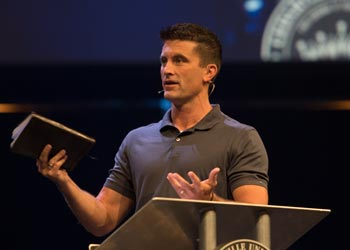A man speaks on a large stage holding a Bible.