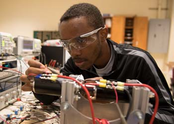 A student works on some electrical components in a room filled with electronics testing equipment