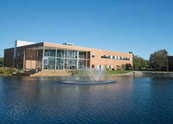 A building with large windows sits along a picturesque lake with a fountain