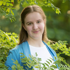 Picture of Sarah Pennington smiling outside in greenery.