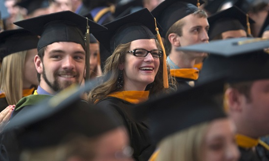 Samuel Walter and Brianna Ahlgrim smile as Dr. William E. Brown addresses the graduating class of 2013. Photo credit: Scott L. Huck/Cedarville University