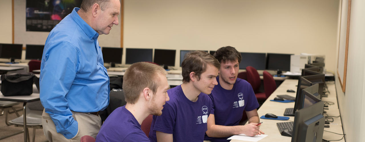 Cedarville student programmers work with professor