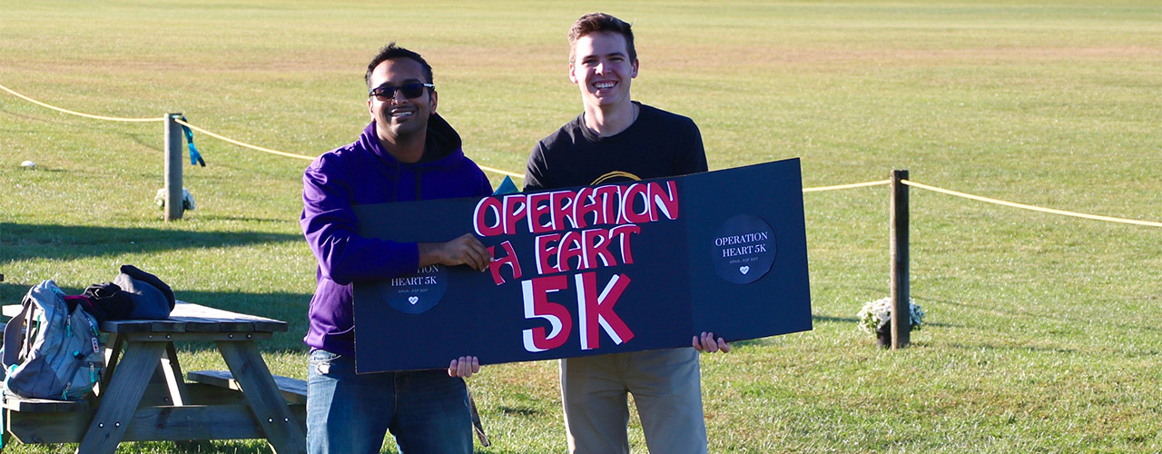 Two young men holding Operation Heart 5K sign