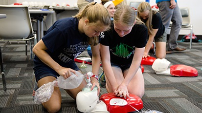 Two Cedarville nursing students perform CPR on a mannequin.