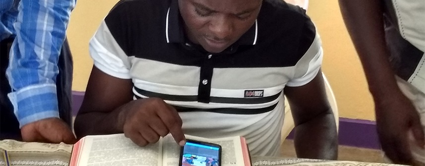 Man reading Bible story on a smartphone.