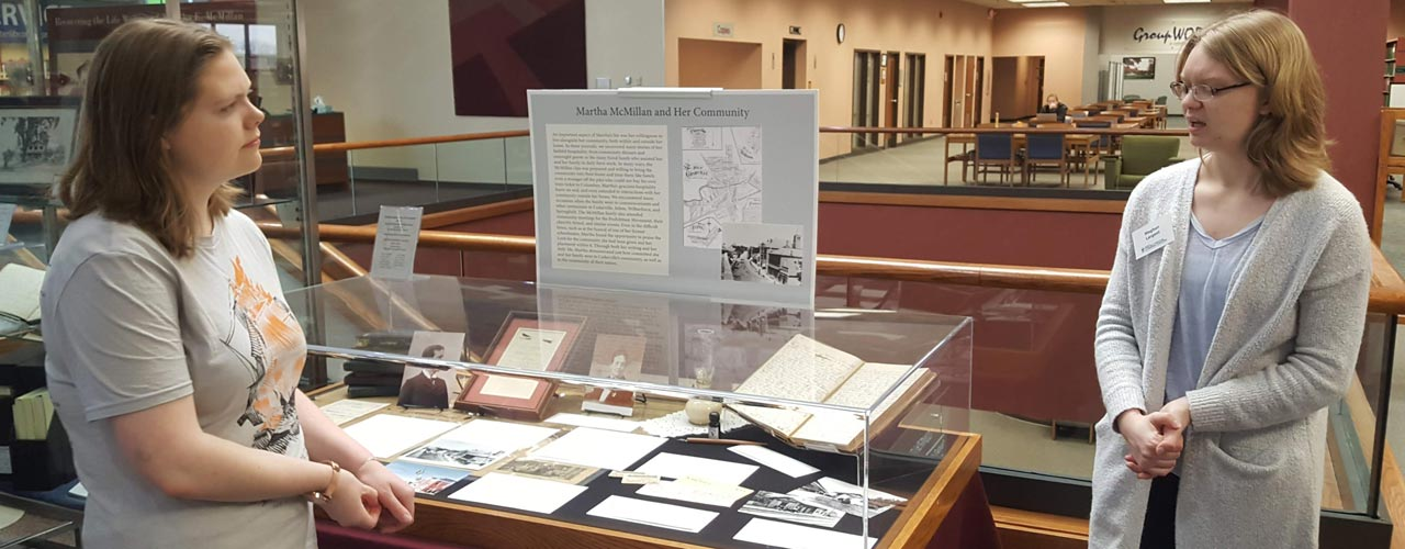 Students discussing Martha McMillan journals at Centennial Library display