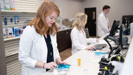 Pharmacy student counting pills inside Cedar Care Pharmacy