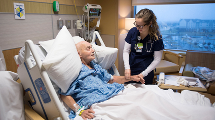 Nursing student working with patient in a hospital room