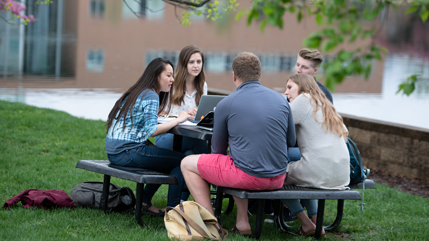 Students sitting at a picnic table next to Cedar Lake