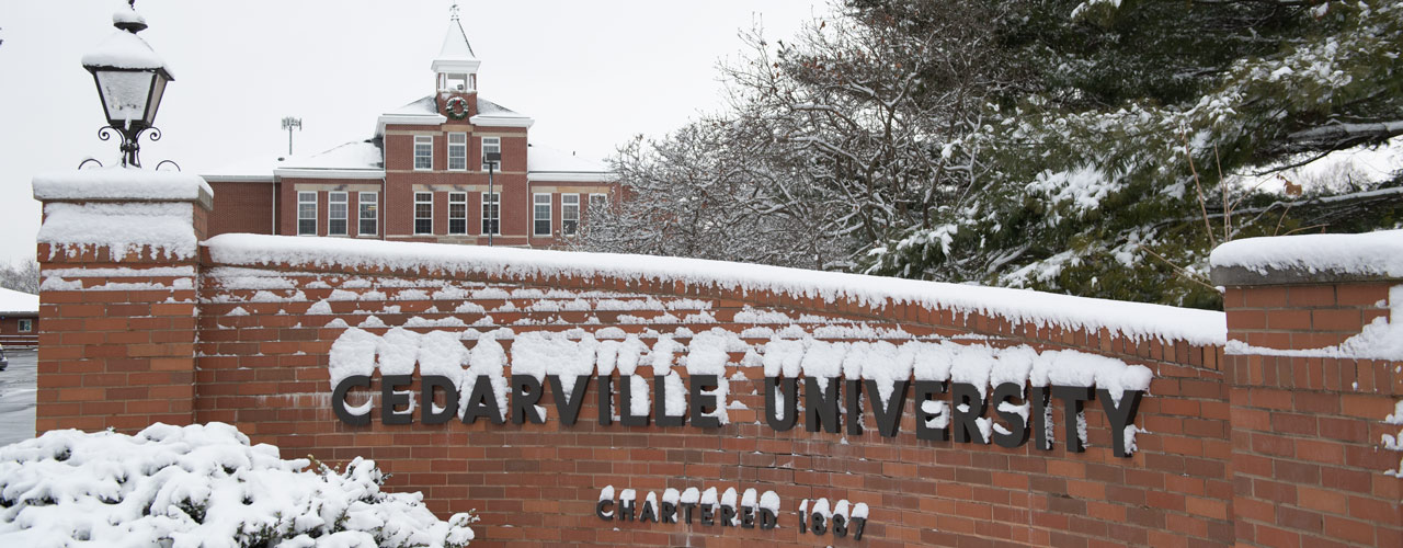 Snowy Cedarville University sign out by St. Rt. 72 with Founders Hall in the background