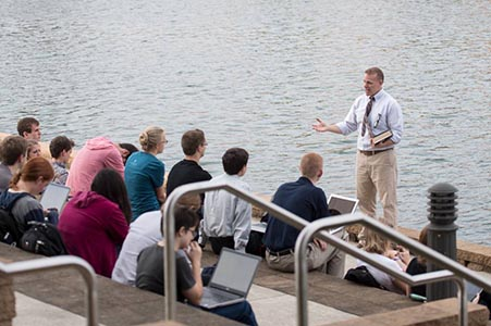 students on the steps of the BTS with a professor teaching with the lake in the background