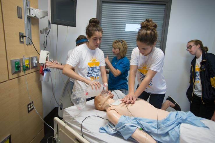 Two female students practice CPR on a mannequin