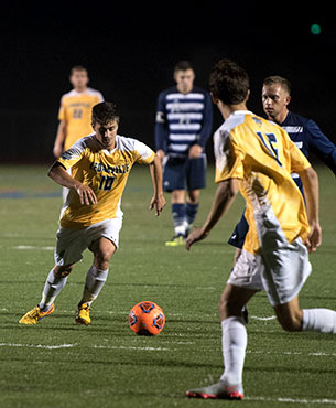 Cedarville soccer player runs up to kick the ball