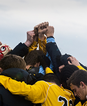 Soccer team members pray together in a huddle with their fists in the air