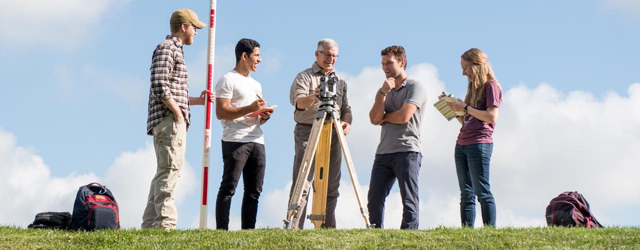 Five people surrounding a surveyors tool