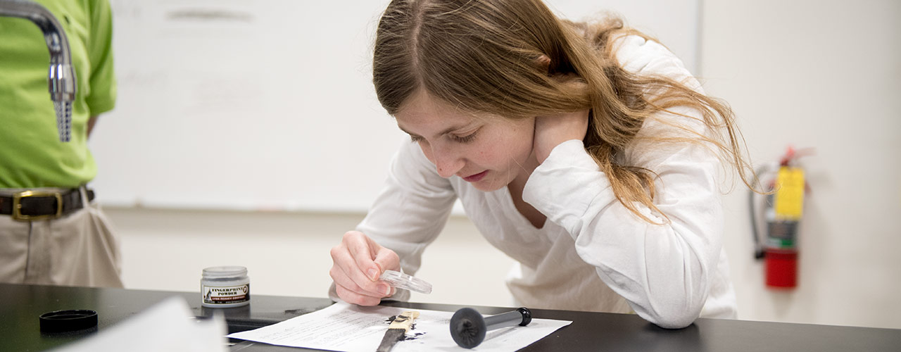 Female criminal justice major uses a magnifying class to observe evidence