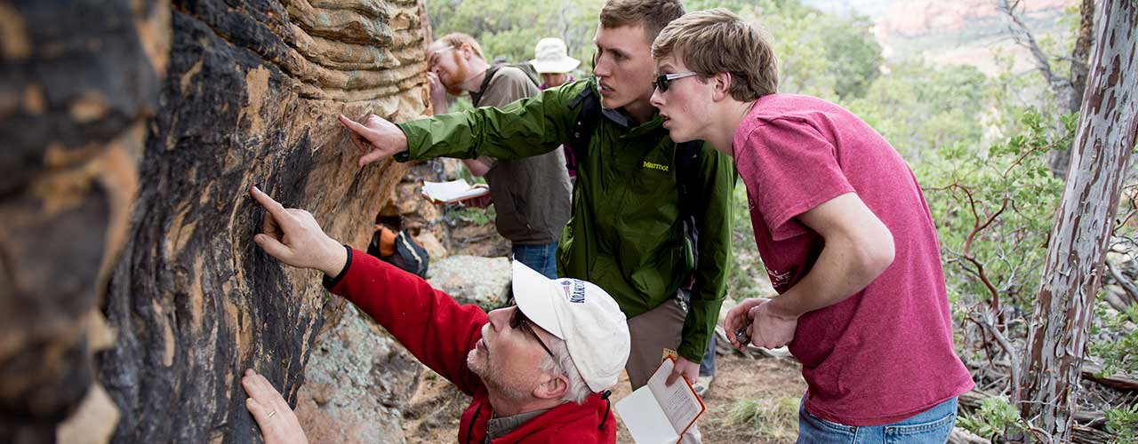 Professor and two geology students examine rock layers