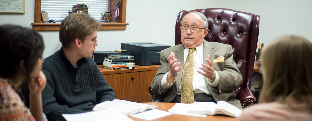 History professor discusses with students in his office
