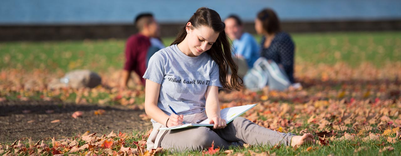 A female liberal arts student sits in leaves while reading a book