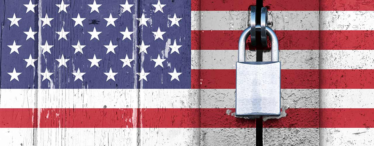 A padlock secures a door painted with the American flag