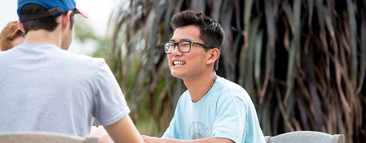Male student smiles while talking with two other students