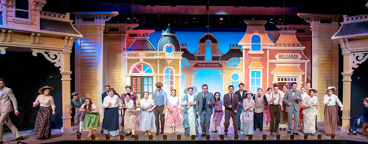 The cast of a Cedarville stage production performs in front of elaborate background