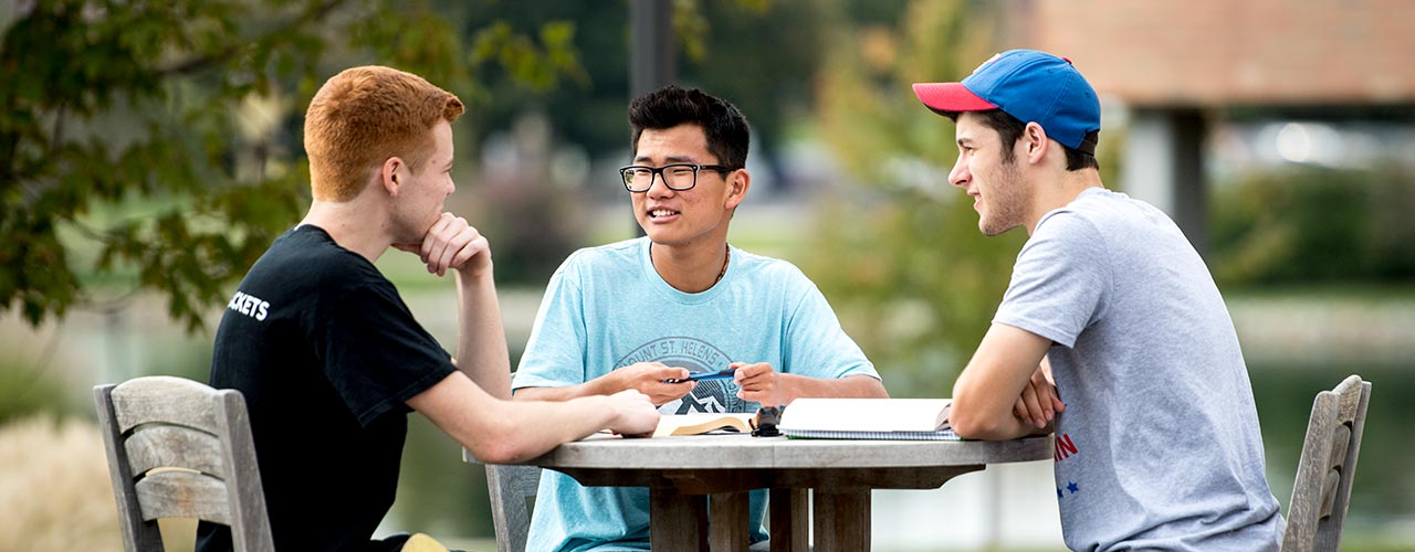 Three male students do homework at a patio table