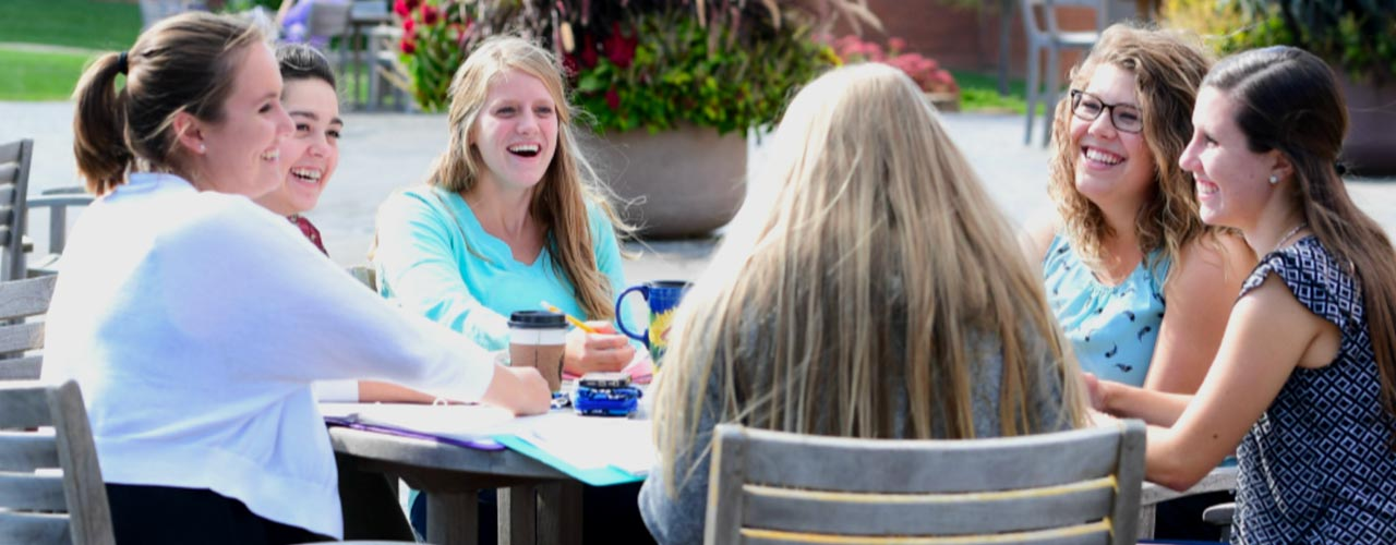 Female students discuss outside around patio table