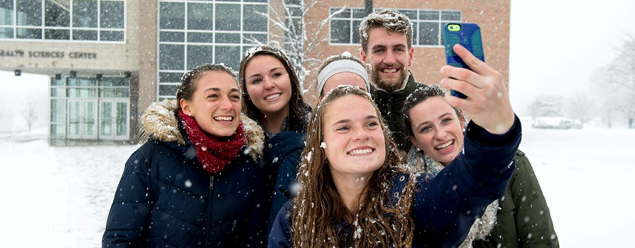 Students take a selfie in the snow outside the Health Sciences Center