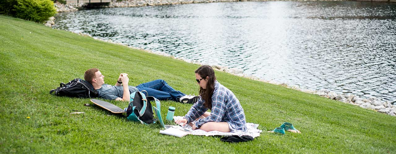 Male and Female student relax by Cedar Lake