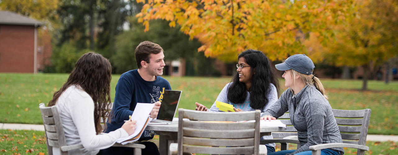Students sitting at an outdoor table conversing with fall foliage in the background.
