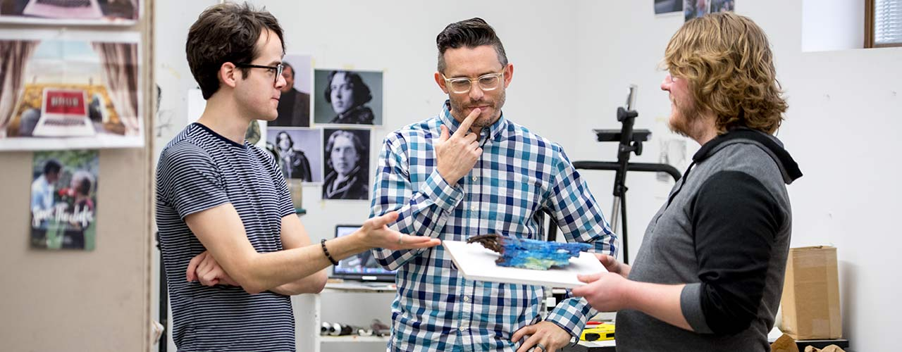 Two male art students consider a piece of art with their professor.