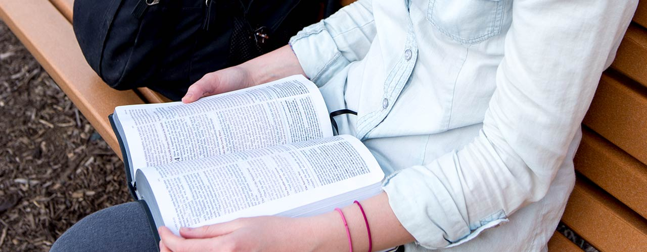 Female student reading her Bible on a park bench