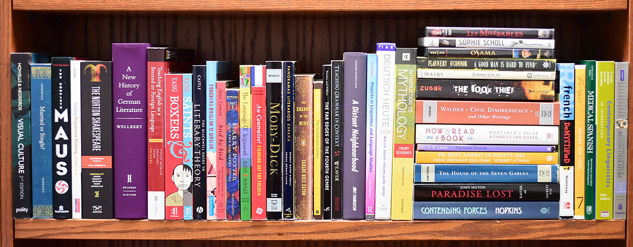 A bookshelf full of a random assortment of books.