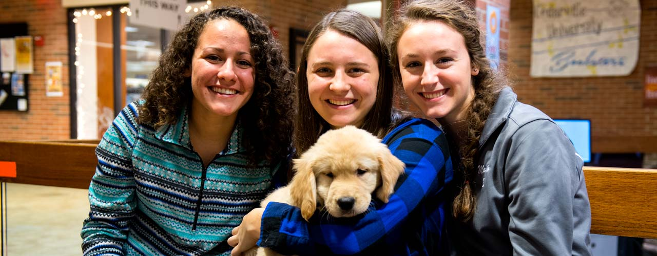 Three female students cuddle with a puppy in the lower Stevens Student Center