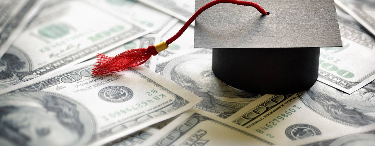 A paper graduation hat sits on money