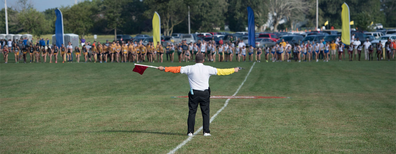 Man with flag and starter gun about to let the line of runners go off to the race