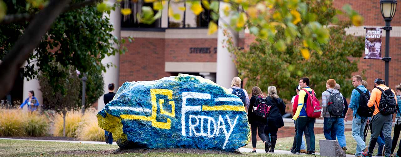 Students walk past the rock painted with CU Friday