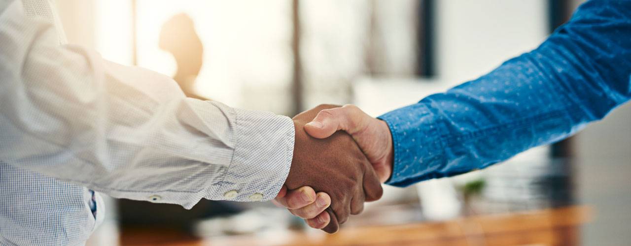 Two men in business attire shake hands