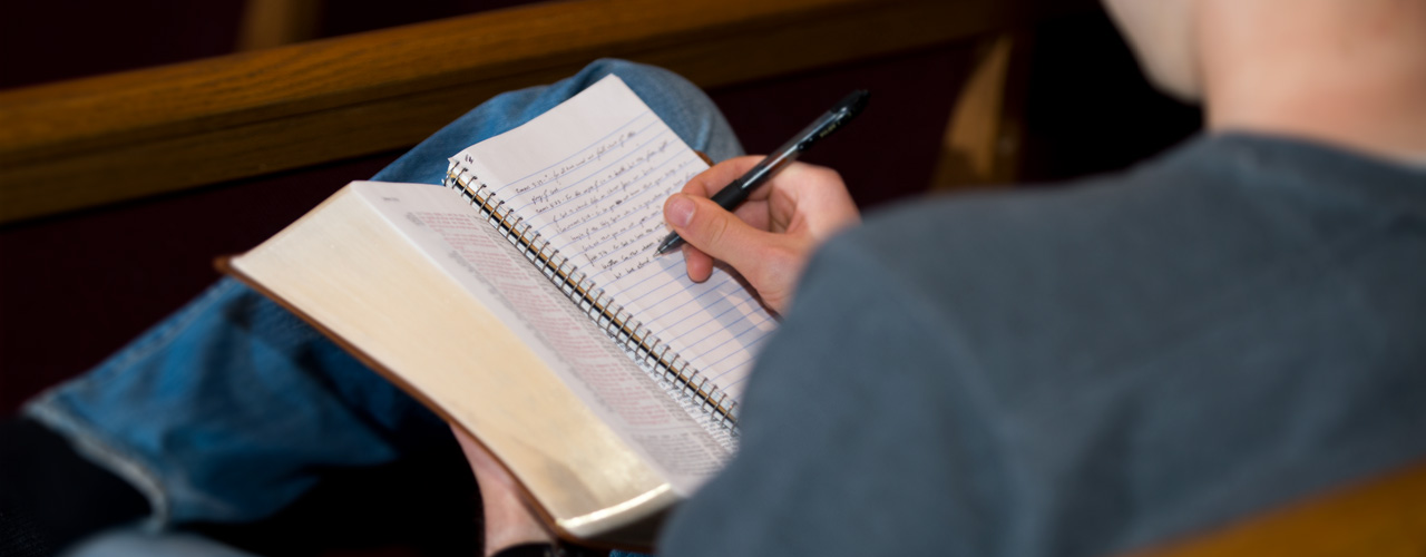 A student takes notes during chapel