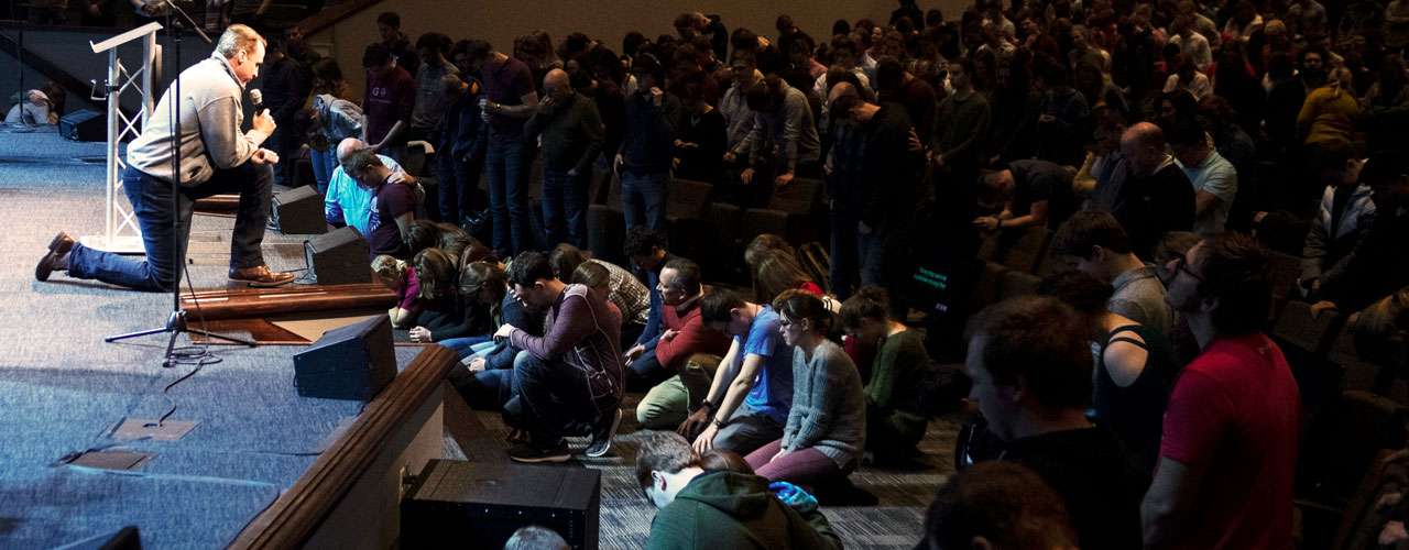 Go Conference attendees standing, speaker on stage kneeling in prayer.
