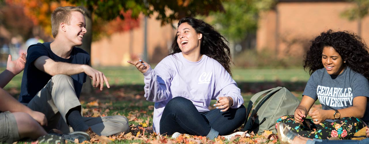 A group of diverse Cedarville students laugh among fall leaves