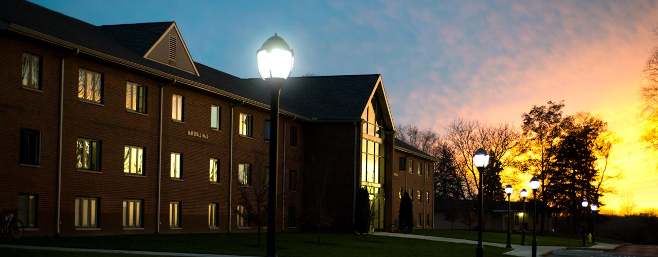 A men's dorm is silhouetted against the sunset