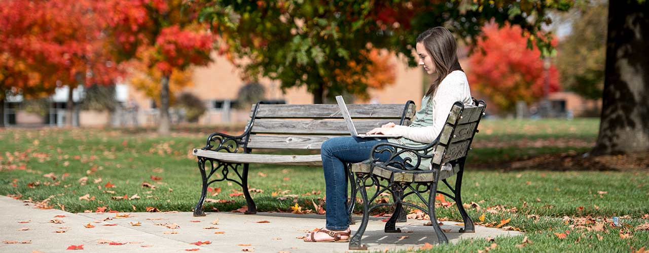 Female student sits on a bench on campus