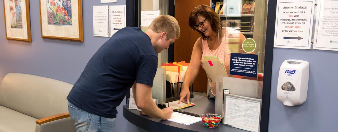 A male student checks in to University Medical Services for an appointment