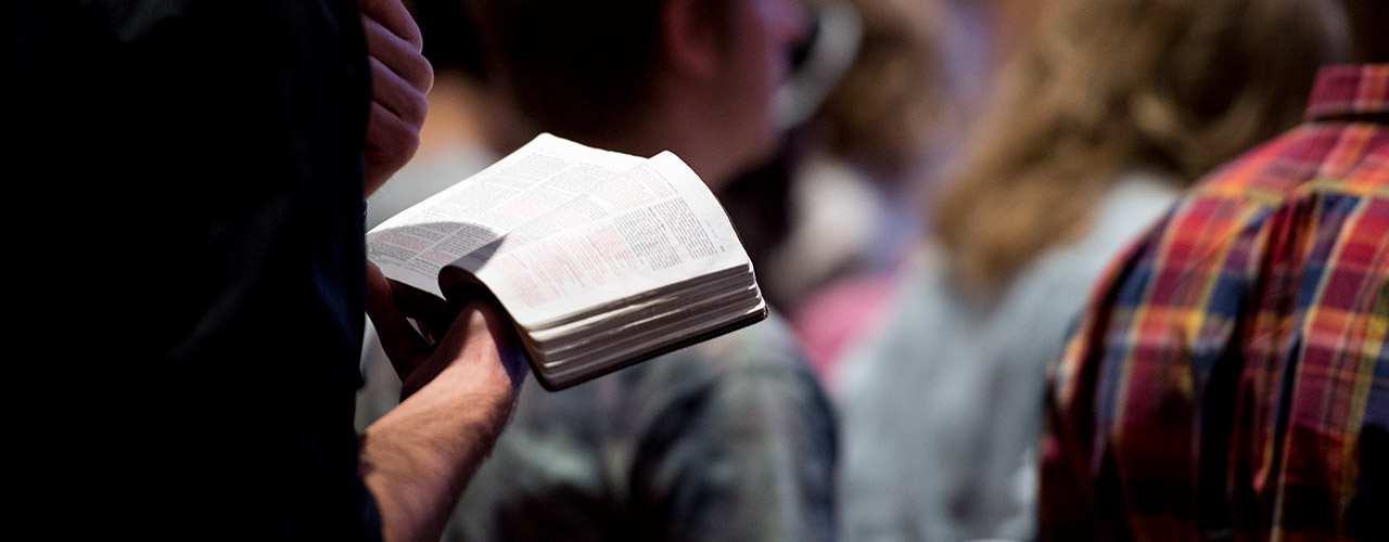Male student reads from Bible during chapel