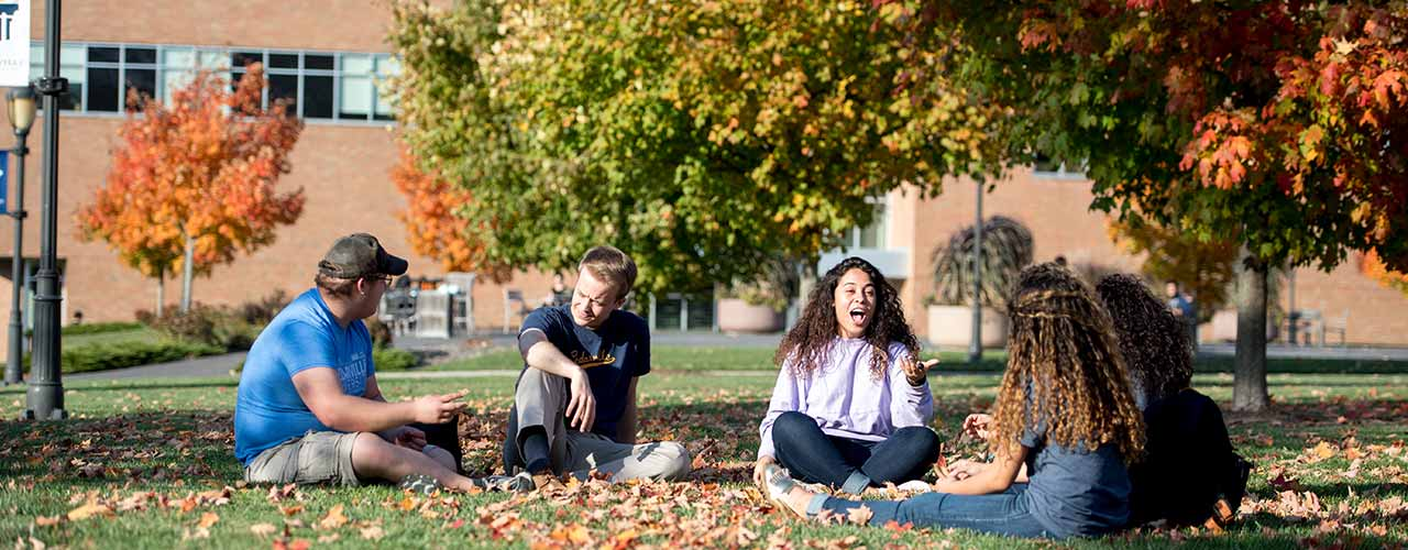 Group of Cedarville students relax in the grass and autumn leaves