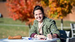 A female student does homework outside in the fall