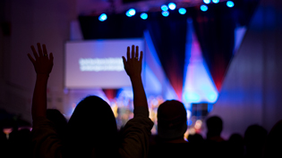 A student raises their hands in worship during chapel