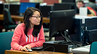 Female student using a computer in Cedarville's library
